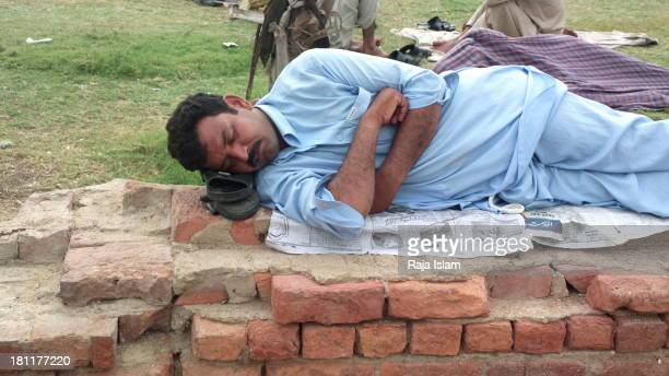 Poor man is sleeping in a public park with his sleepers under his head to avoid them get robbed.