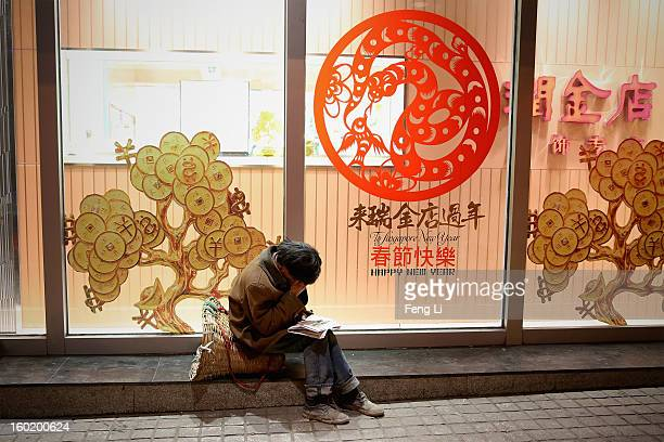 Poor man sits outside a department store on January 27, 2013 in Guiyang of Guizhou Province, China.