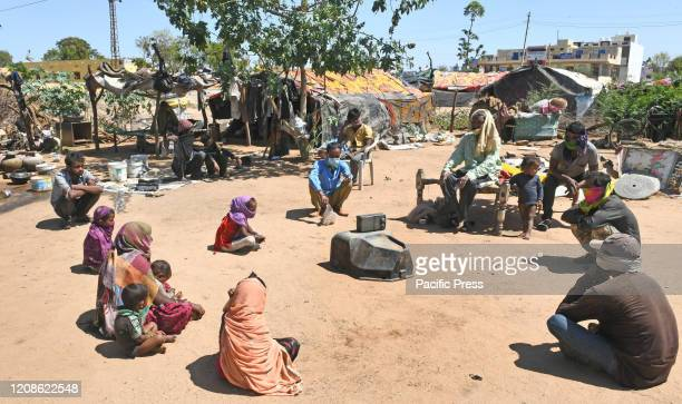 Poor people listen to Prime Minister Narendra Modi's radio program 'Mann Ki Baat' on Coronavirus pandemic at a slum area in Beawar