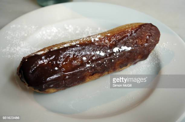 Poor quality chocolate eclair with melted icing on a round white plate