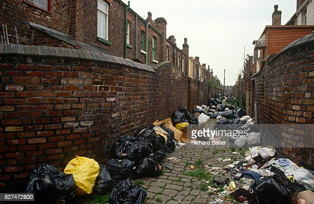 Poor terraced housing and alleyway in Liverpool with black refuse bags left against poor housing brick walls Surrounded by black binbags during the...