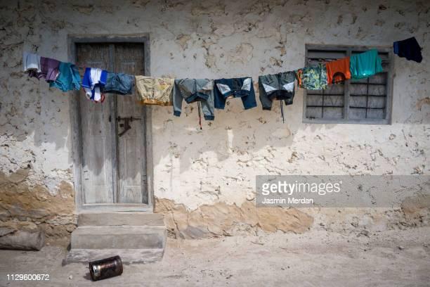 poor village house in africa with clothesline - omgeven stockfoto's en -beelden