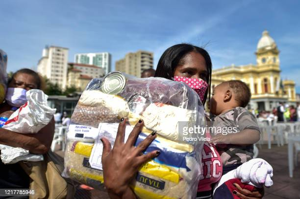 Poor woman and child in line to pick up fruit at Praça da Estação on June 5, 2020 in Belo Horizonte, Brazil. About 3000 meals are being distributed...