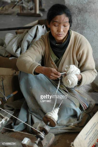 Poor Woman Spinning Yarn. Rug Industry in Asia.