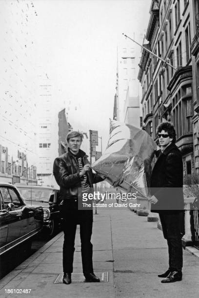 Pop artist Andy Warhol and rock singer musician and songwriter Lou Reed pose for a portrait with one of Warhol's iconic pop sculptures a helium...