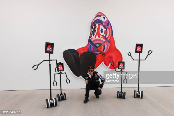 Pop artist Philip Colbert accompanied by robots enlisted to allow digital users to explore the exhibition via their smartphone or computer poses next...