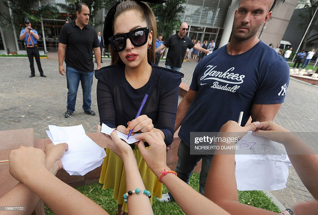 US pop diva Lady Gaga (c) signs autographs to fans outside the hotel, in Asuncion, on November 26, 2012. Lady Gaga, currently on tour in South America, will offer a show tonight in the Paraguayan capital.