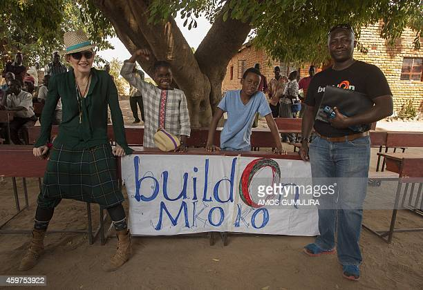 US pop diva Madonna and her Malawian adopted Children Mercy James and David Banda pose with NGO BuildOn director Maurice Muchene during a visit to...