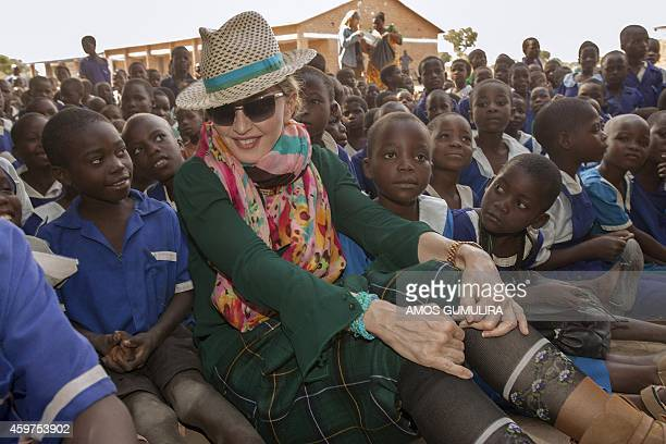 US pop diva Madonna sits among Malawian children during a visit to the Mkoko Primary School one of the schools Madonna's Raising Malawi organization...