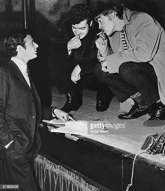 Pop group manager Brian Epstein with actors Michael Blackham and Hywel Bennett at rehearsals of the play 'A Smashing Day' by Alan Plater at the New...