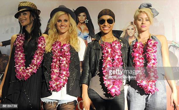 US pop group Pussycat Dolls Nicole Scherzinger Ashley Roberts Melody Thornton and Kimberly Wyatt pose infront of a poster after arriving at the...