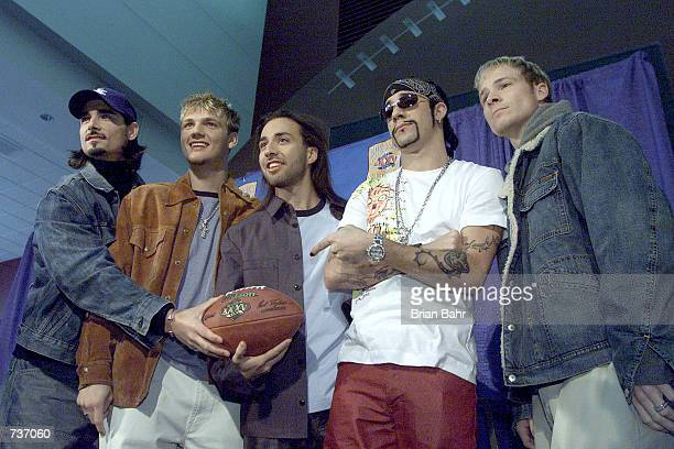 Pop group The Backstreet Boys poses with a football during a press conference for performers in the 2001 Super Bowl XXXV pregame show at Raymond...