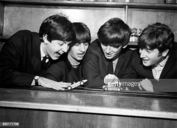 Pop Group The Beatles John Lennon Paul McCartney Ringo Starr George Harrison The Beatles in Coventry amusing themselves with a miniture car race...