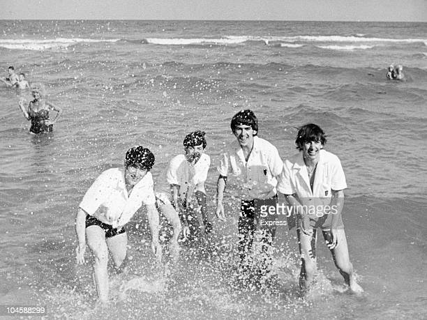 Pop group The Beatles relax on a beach in Miami Florida From left to right John Lennon Paul McCartney George Harrison and Ringo Starr circa February...