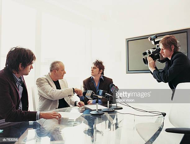 Pop Musician Shaking Hands With a Businessman at a News Conference With Microphones and a TV Cameraman