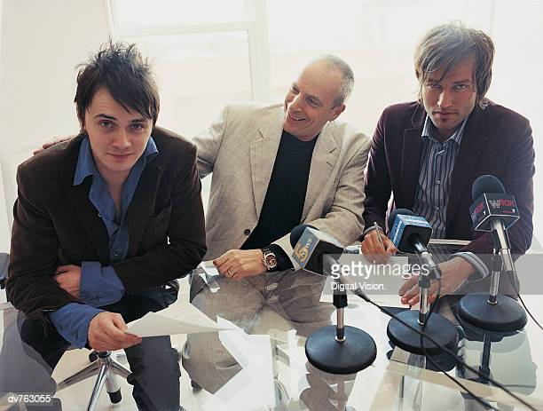 Pop Musicians Signing a Contract at a News Conference With Their Manager With His Hand on One of Their Shoulders