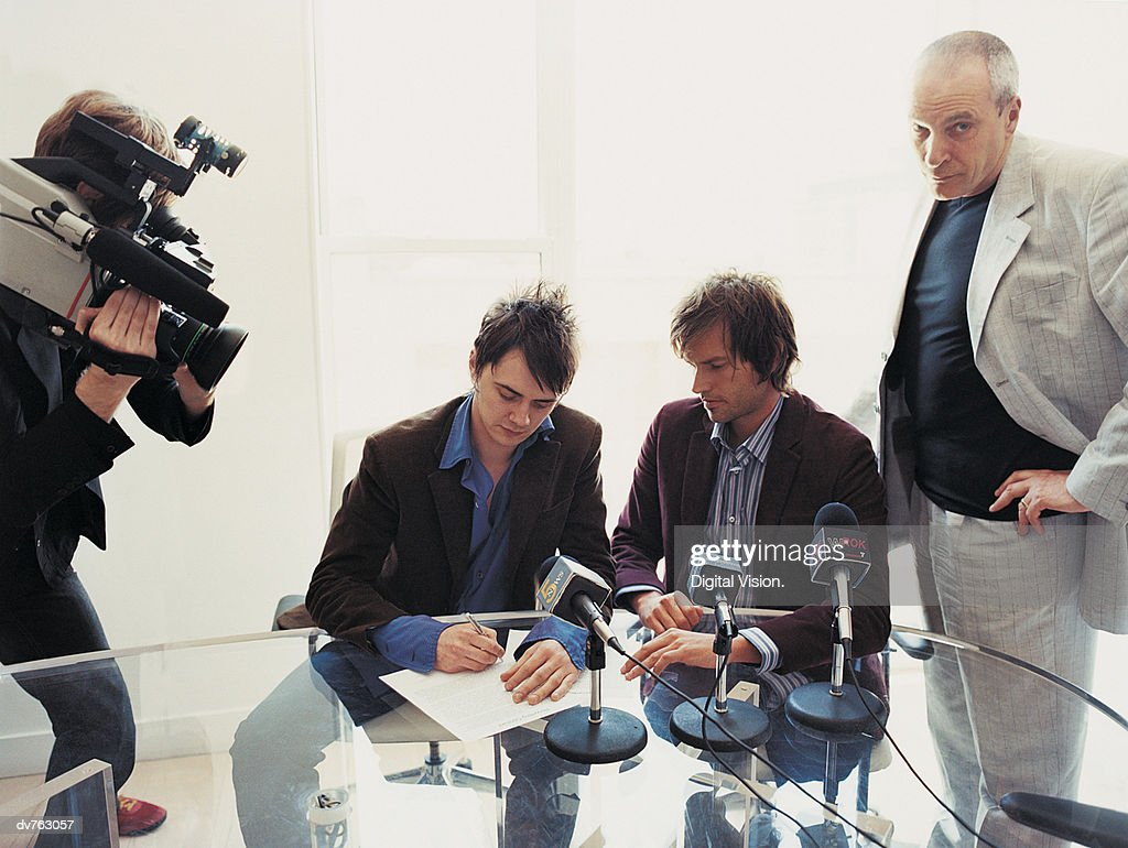 Pop Musicians Signing a Contract in a Conference Room Attended by Their Manager and a TV Cameraman : Stock Photo