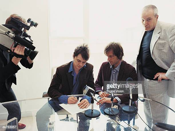 Pop Musicians Signing a Contract in a Conference Room Attended by Their Manager and a TV Cameraman