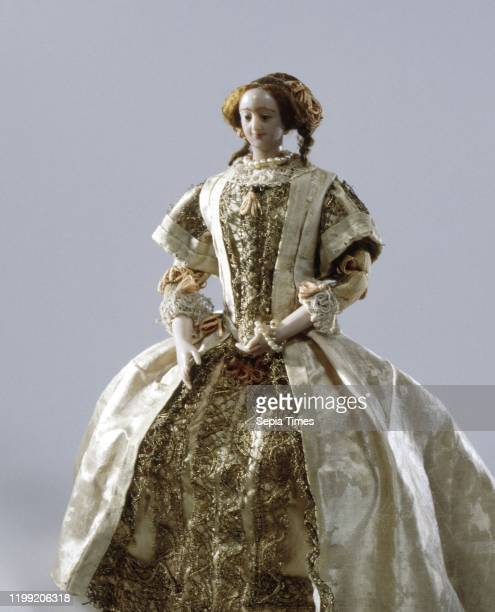 Pop, representing a miss, dressed in a frock consisting of three parts, a breast piece of plain cream silk, a skirt of plain originally pink-red...