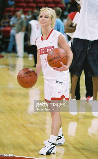 Pop singer Britney Spears dribbles a basketball during warmups for NSync''s Challenge for the Children III charity event July 29 2001 at the Thomas...