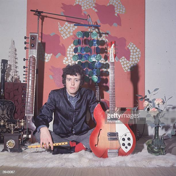 Pop singer Donovan holding his Rickenbacker guitar and a flute a sitar and other guitars in the background