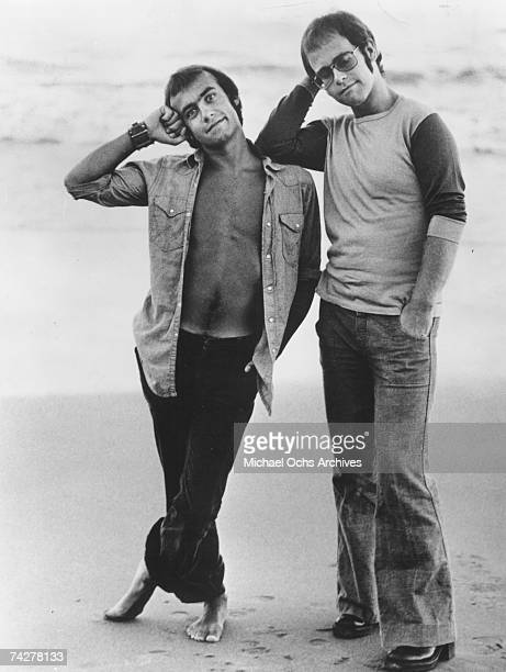 Pop singer Elton John leans up against his songwriting partner lyricist Bernie Taupin on the beach as they pose for a portrait in circa 1972