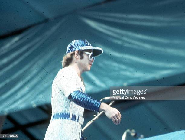 Pop singer Elton John performs onstage at Dodger Stadium in a blue and white sequined outfit Dodgers uniform on October 25, 1975 in Los Angeles,...