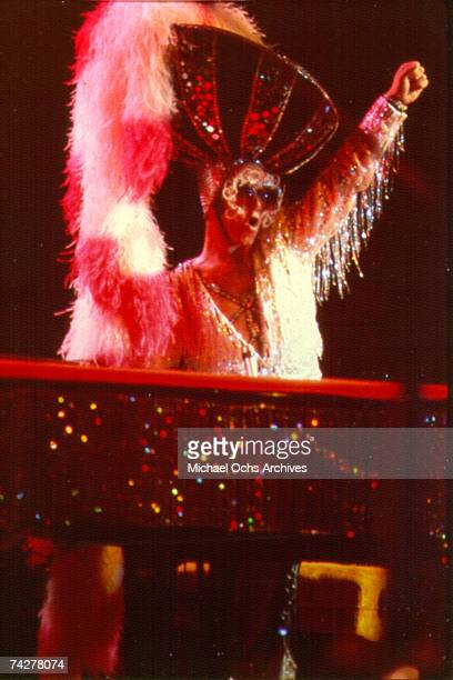 Pop singer Elton John performs onstage at the piano wearing a giant fuzzy hat in circa 1974.
