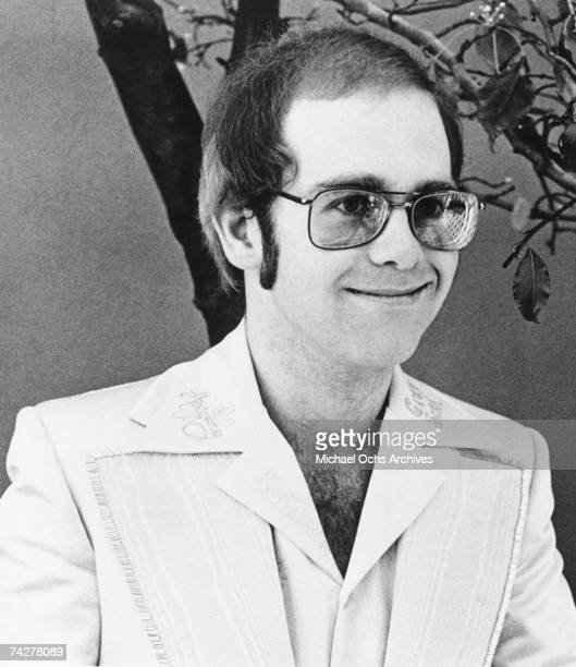 Pop singer Elton John poses for a portrait wearing a 1970's style leisure suit in circa 1977