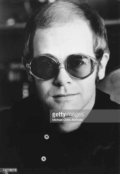 Pop singer Elton John poses for a portrait wearing glasses in circa 1972