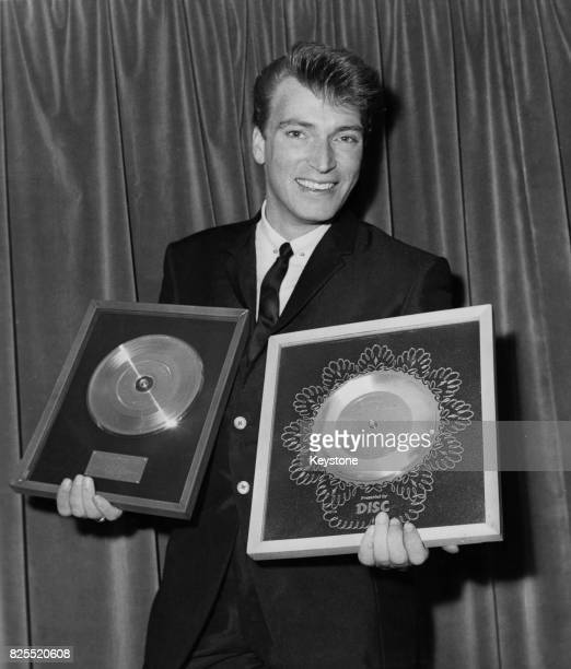 Pop singer Frank Ifield receives a Golden Disc for his song 'I Remember You' and a Silver Disc for 'Lovesick Blues' as a 25th birthday present from...