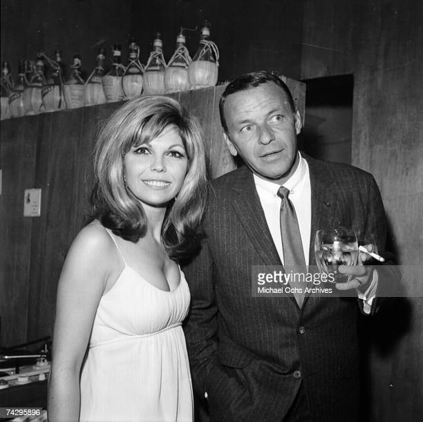 Pop singer Frank Sinatra enjoys a cocktail at an event with his daughter singer Nancy Sinatra in circa 1967