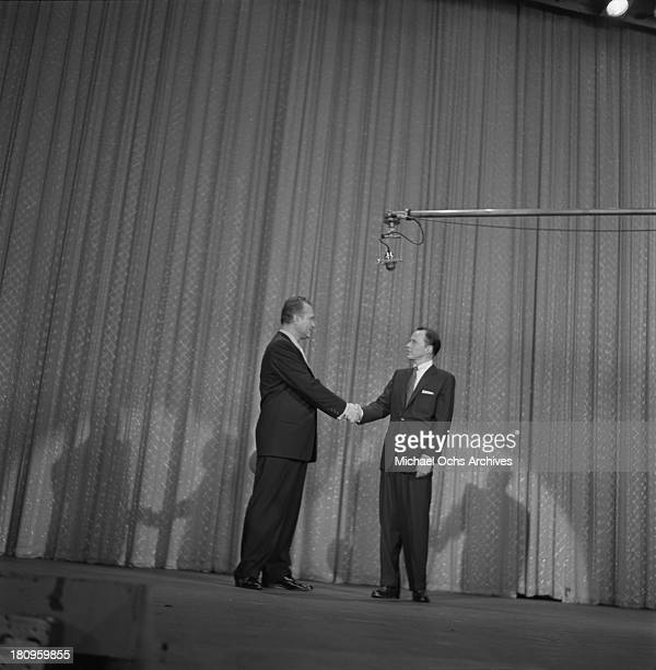 Pop singer Frank Sinatra greets guest host Red Skelton on the Ed Sullivan Show on August 19, 1956 in New York City, New York.