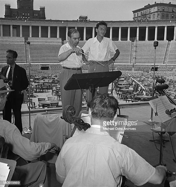 Pop singer Frank Sinatra performs onstage during a soundcheck with Max Steiner conducting the orchestra at Lewisohn Stadium on August 3 1943 in New...