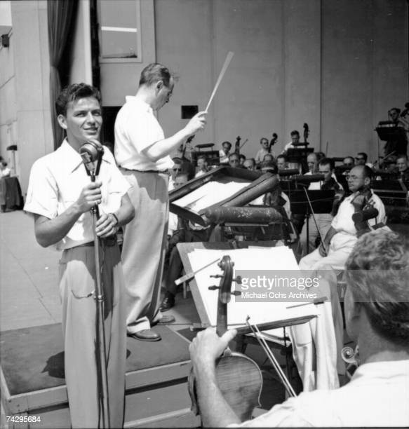 Pop singer Frank Sinatra performs onstage during a soundcheck with Max Steiner conducting the orchestra at Lewisohn Stadium on August 3, 1943 in New...