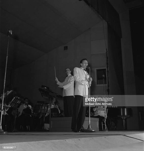 Pop singer Frank Sinatra performs onstage with Max Steiner conducting the orchestra at Lewisohn Stadium on August 3, 1943 in New York City, New York.