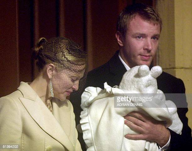 Pop singer Madonna looks down at her son Rocco held by film director Guy Ritchie as they leave Dornoch Cathedral 21 December 2000 The couple...