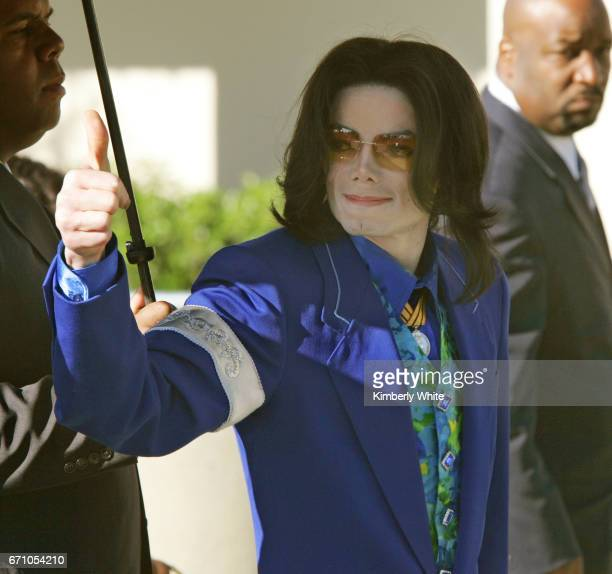 Pop singer Michael Jackson gestures as he enters the Santa Barbara County Court in Santa Maria with his bodyguards during the third week of his child...