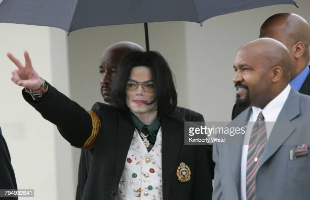 Pop singer Michael Jackson gestures as he leaves the Santa Barbara County Courts with his bodyguards for the third day of his child molestation trial...