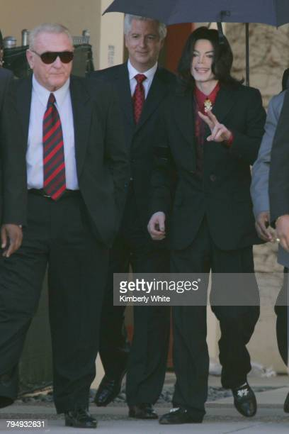 Pop singer Michael Jackson gestures to fans next to his attorney Brian Oxman after leaving the Santa Barbara County Courthouse Superior Court Judge...