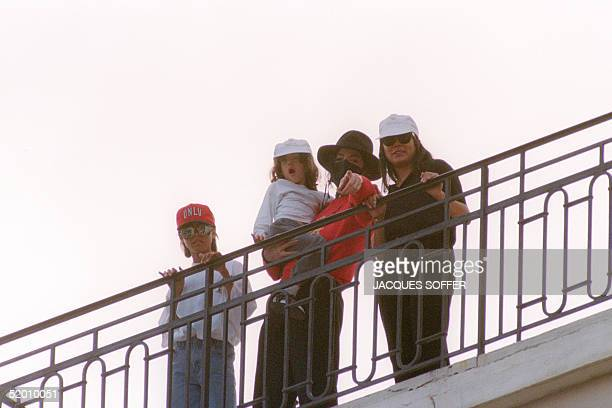 US pop singer Michael Jackson holding an unidentified child points 09 May 1993 to fans in Monaco