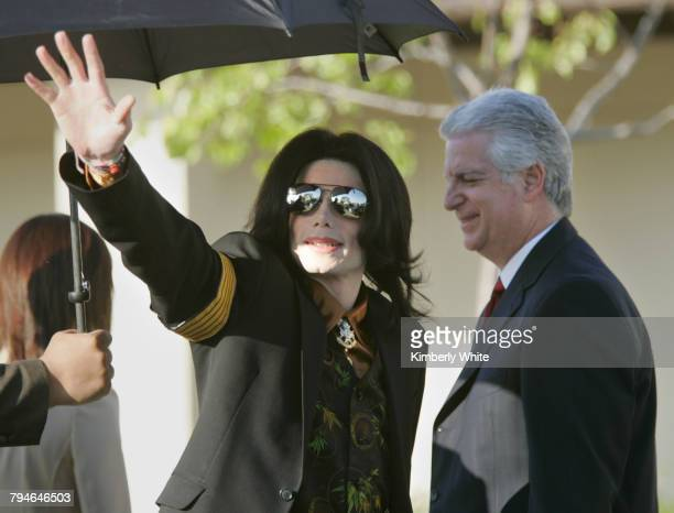 Pop singer Michael Jackson waves to fans as he stands next to his attorney Brian Oxman while he enters the Santa Barbara County Courthouse Yesterday...