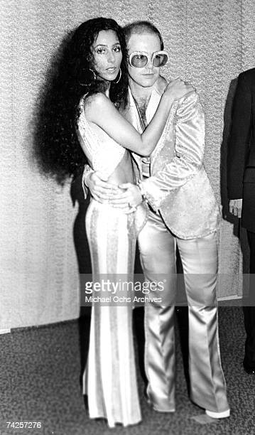 Pop singers Cher and Elton John pose for a portrait backstage at an awards show in circa 1975