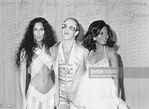Pop singers Cher Elton John and Diana Ross pose for a portrait backstage at an awards show in circa 1975
