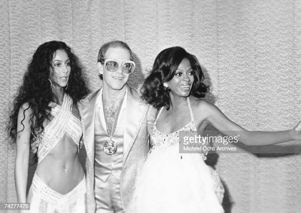 Pop singers Cher Elton John and Diana Ross pose for a portrait backstage at the first Rock Music Awards which were held at the Santa Monica Civic...