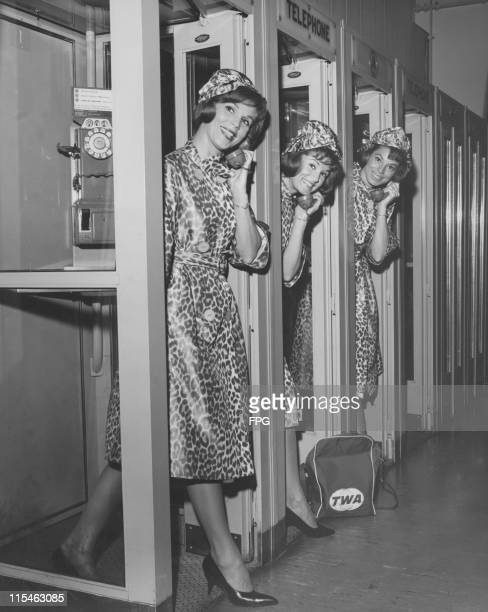 Pop singers the McGuire Sisters pose wearing leopard skin print outfits in telephone booths at New York International Airport in New York City New...