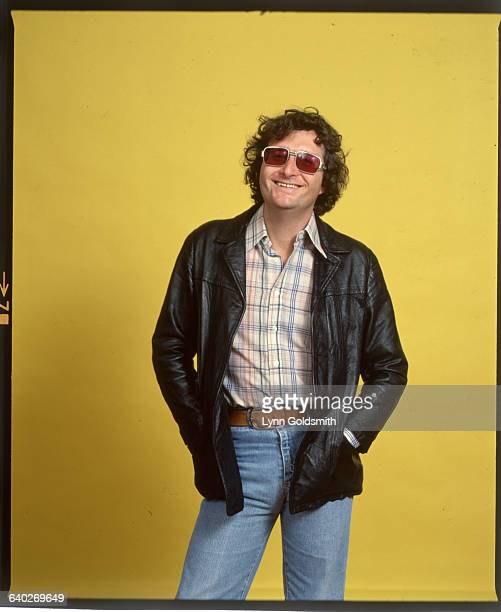 Pop singer/songwriter Randy Newman is shown in a 3/4 length studio portrait smiling and wearing sunglasses Undated