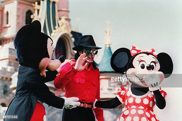 US pop star and entertainer Michael Jackson flanked by Mickey Mouse and Minnie waves to fans July 27 1992 during his suprise visit to the EuroDisney...