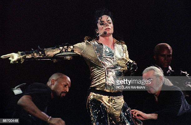 US pop star and entertainer Michael Jackson gets a helping hand from his crew stripping out of his space suit on October 25 1996 in Singapore Michael...