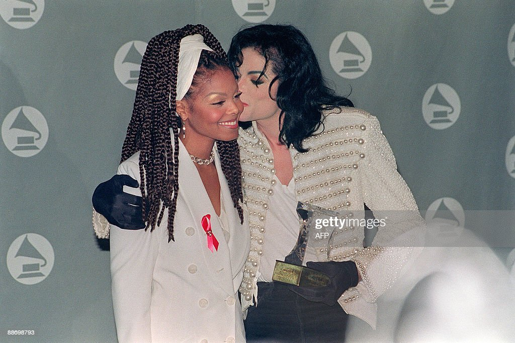 US pop star and entertainer Michael Jackson kisses his sister Janet Jackson (L) after she presented him with the Grammy Legend Award at the 35th Annual Grammy Awards Febuary 24,1993. Michael Jackson died on June 25, 2009 after suffering a cardiac arrest, sending shockwaves sweeping across the world and tributes pouring in on June 26 for the tortured music icon revered as the 'King of Pop.' AFP PHOTO/Scott FLYNN